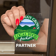 Green farm and red barn circle graphic on clear square Local Food Fresher! custom window decal on glass