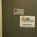 Yellow lightbulb and black text on white vinyl rectangle JD Electric weatherproof label on electrical box