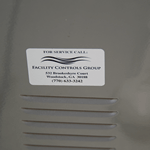 Black text and wavy lines on white vinyl rectangle Facility Control Group weatherproof label on heating unit
