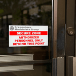 Red text and gray gear on white vinyl rectangle Greensboro Machinists Group Secure<br/>Zone weatherproof label on glass door