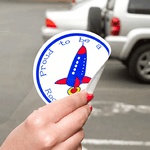 Blue and red rocket graphic on white circle Proud To Be custom static cling decal on window